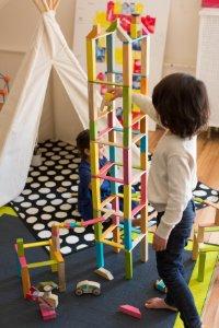 Мальчик строит башню из деревянного конструктора с магнитами