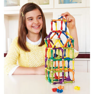 Девочка собирает башню из магнитного конструктора