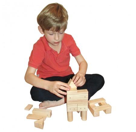 Мальчик играет с деревянным конструктором