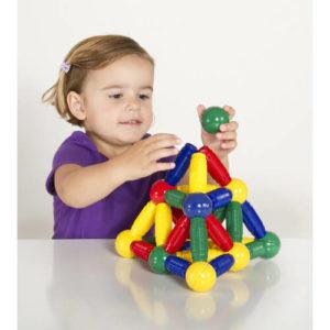 Маленькая девочка играет в магнитный конструктор